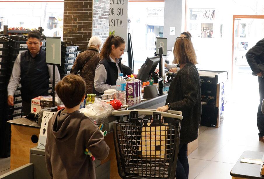 Consumidores en una cola en un supermercado.