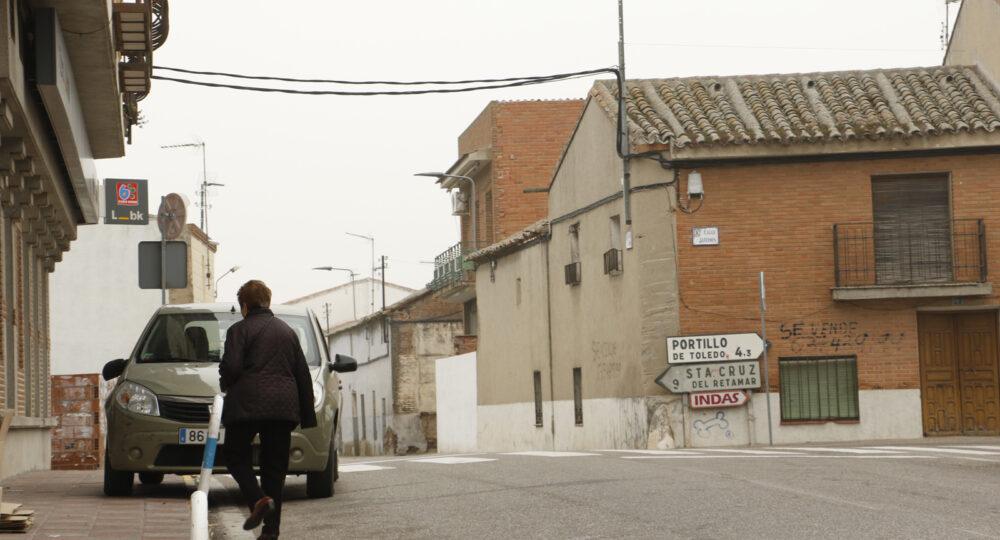 Una mujer camina por un pueblo.