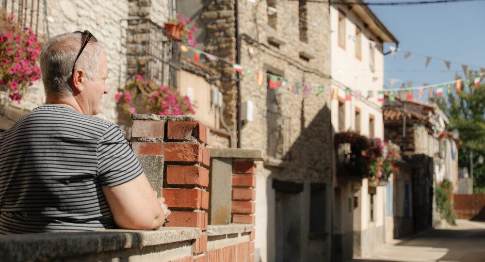 Una mujer en su patio contempla la calle de su pueblo en la provincia de Soria. Autor: Joaquín Terán.