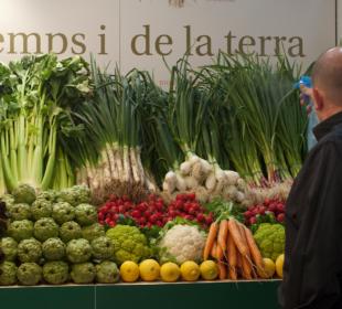 Un comerciante cuida sus verduras en un puesto en un mercado de Barcelona. Foto: EDR.