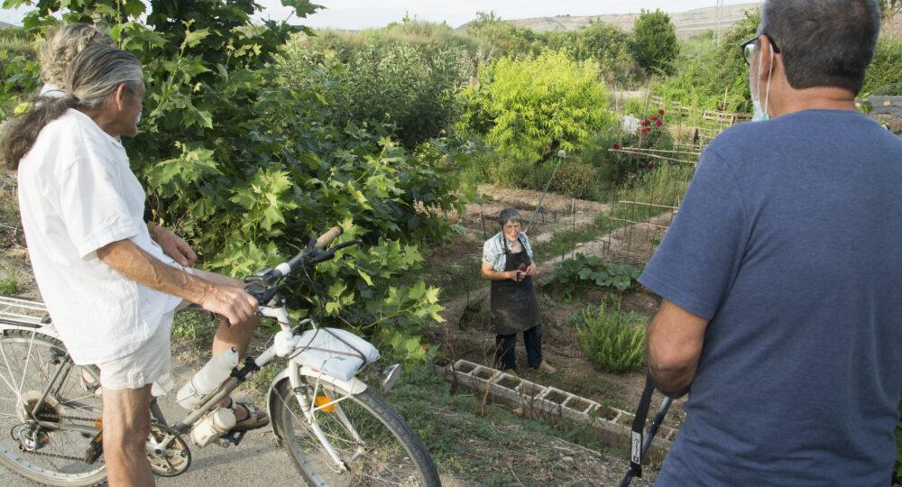 Ciudadanos de Alcanadre (La Rioja) conversan en la huerta de Práxedes. Foto: EDR.